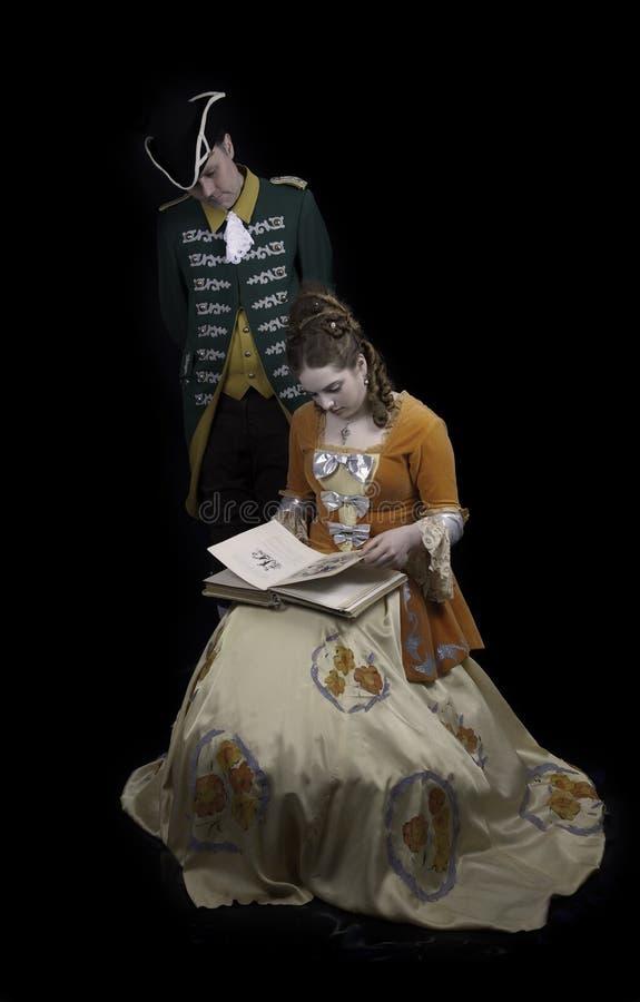 Barok paar met riet bedekkend boek royalty-vrije stock afbeeldingen