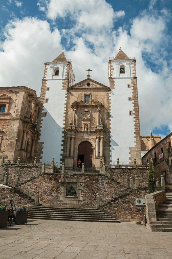 Barokke kerkvoorgevel met steentrap en standbeeld van St George in Caceres stock afbeelding