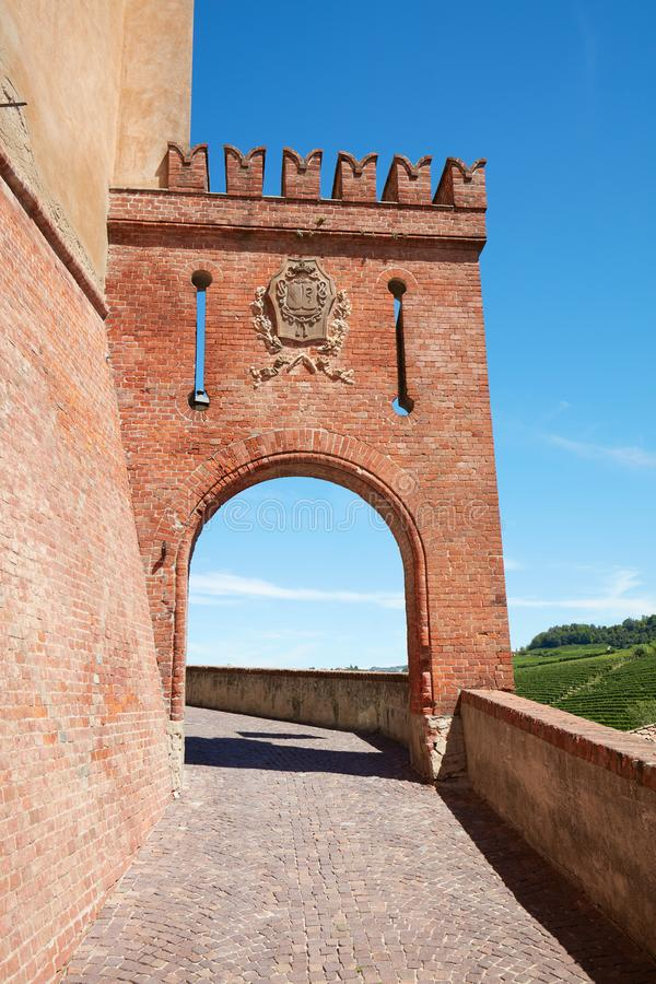 Barolo medieval castle entrance arch and empty street in Italy. BAROLO, ITALY - AUGUST 6: Barolo medieval castle entrance arch in red bricks and emblem with royalty free stock image