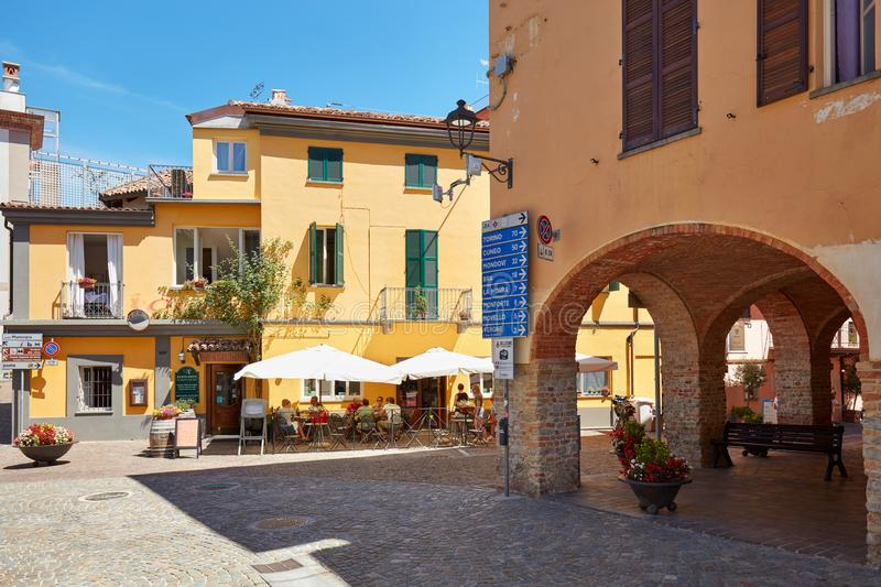 Barolo streets, arches and sidewalk restaurant in a sunny summer day in Italy royalty free stock photography