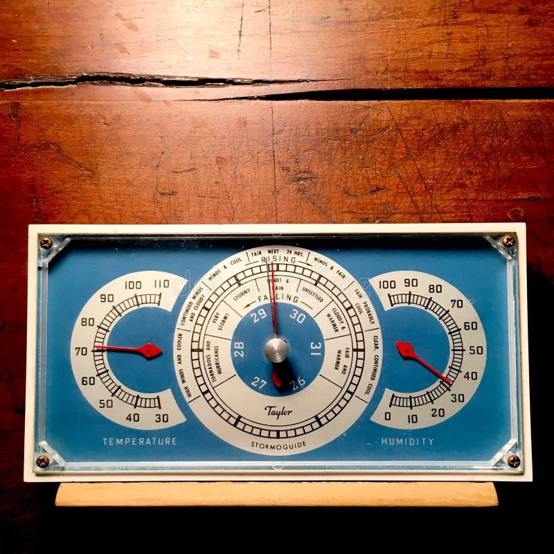 Barometro d'annata con il termometro e l'igrometro, indicati contro un fondo di legno stagionato immagini stock