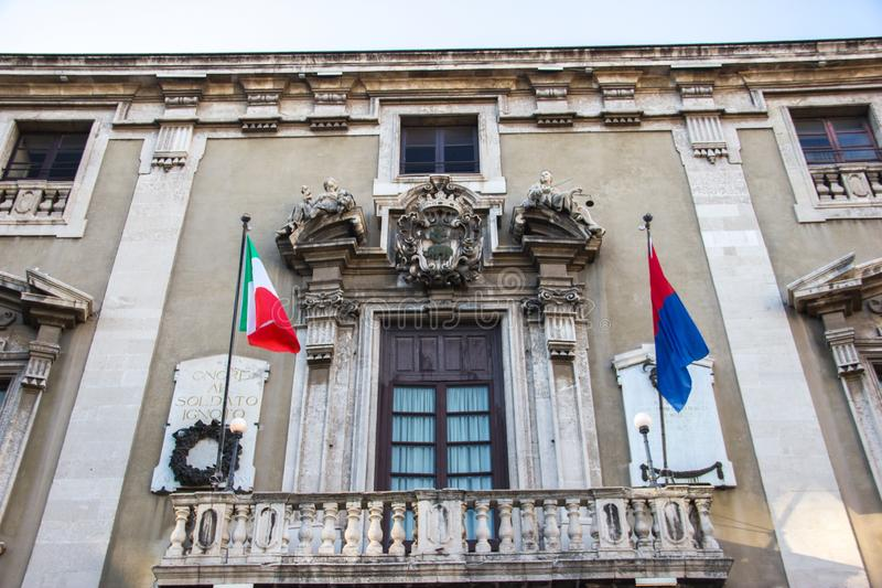 Catania baroque architecture, historical building, ornament in balcony. Baroque art in a historical building and balcony in Catania, ornament and flags stock images
