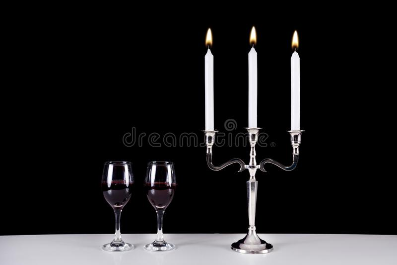 Baroque candlestick and two red wine glasses on white table stock images