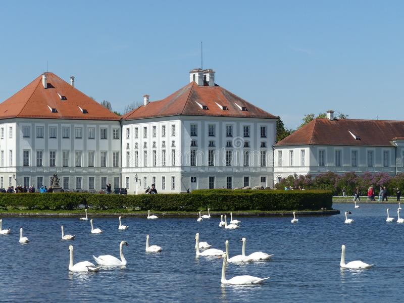 Baroque castle of Nymphenburg with  a small lake and white swans. Munich, Germany. royalty free stock photography
