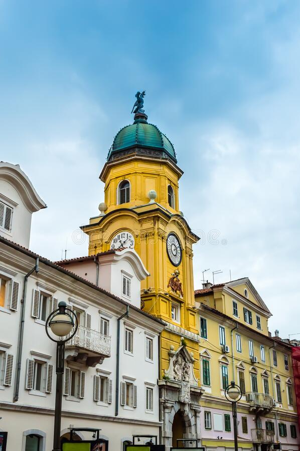 Yellow City Clock Tower in the center of Rijeka, Croatia. Baroque City Clock Tower painted in yellow on a sunny day. Colorful old buildings with rows of windows stock photo