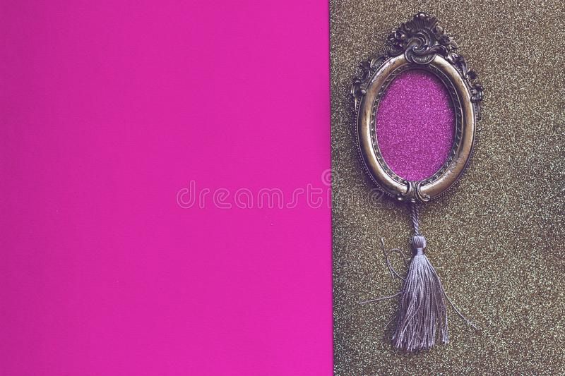 Baroque oval golden picture frame on pink and golden background stock photography