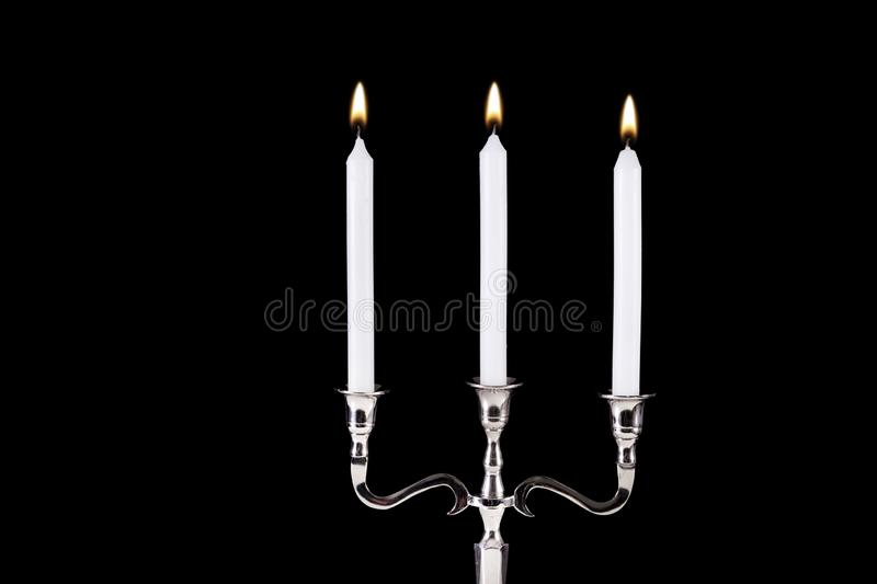 Baroque silver candlestick with white paraffin candles burning isolated on black background royalty free stock photo