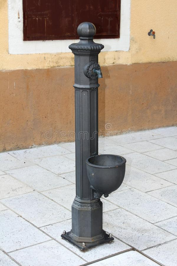 Baroque style iron pipe serving as hand water pump mounted on stone tiles of local town square next to old family house stock photo