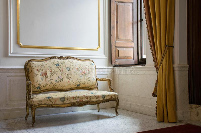 Baroque style sofa near window. Classic interior with marble floor and white,gold walls. Castle hall. Romantic interior style. royalty free stock photo
