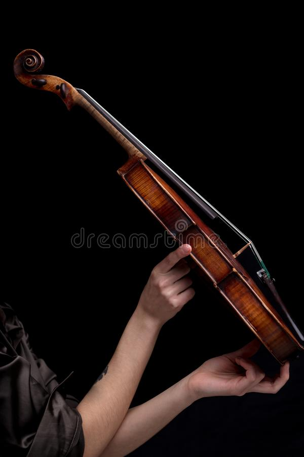 Baroque violin held by woman`s hand. On a black background royalty free stock images