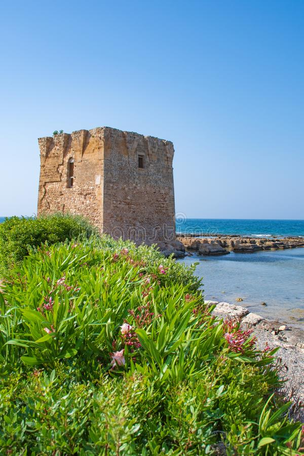 Baroque watchtower, beautiful old tower in San Vito, Polignano a Mare, Bari, Puglia, Italy with with blue sea. Stone wall and flowers, Mediterranean landscape royalty free stock photography