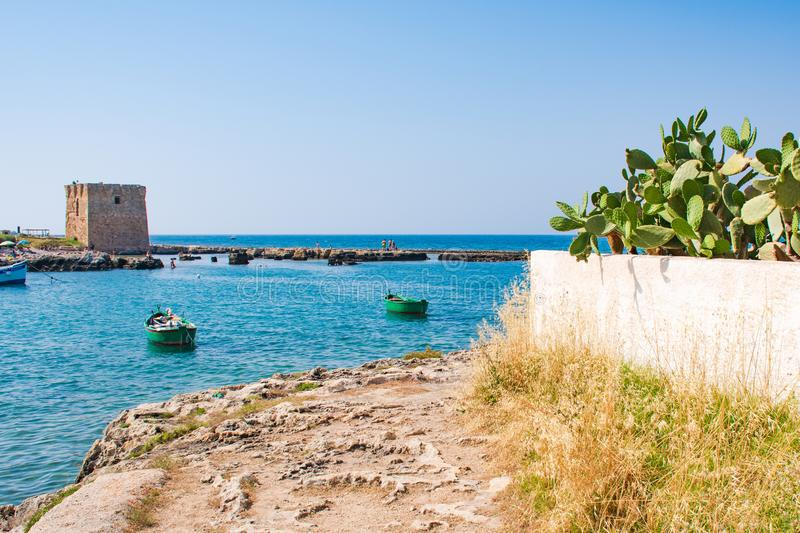 Puglia, Mediterranean landscape. Baroque watchtower, beautiful old tower in San Vito, Polignano a Mare, Bari, Puglia, Italy with with blue sea, wooden boats stock photos