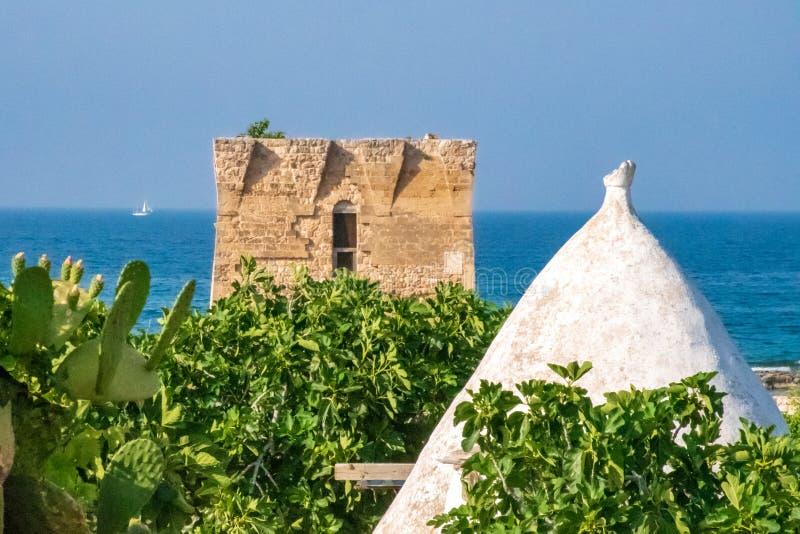 Mediterranean landscape, Puglia. Baroque watchtower, beautiful old tower in San Vito, Polignano a Mare, Bari, Puglia, Italy with with trullo, blue sea, beach and stock photos