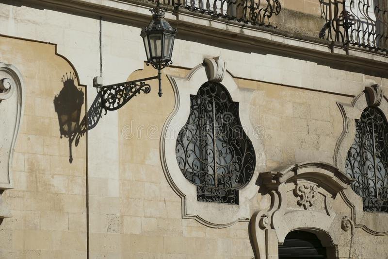 Baroque wrought iron windows and doors. On limestone palaces of Lecce, Puglia, Italy stock images