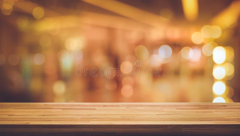 Barra contrária do tampo da mesa de madeira da textura com bokeh claro do ouro do borrão no fundo do café da noite foto de stock royalty free