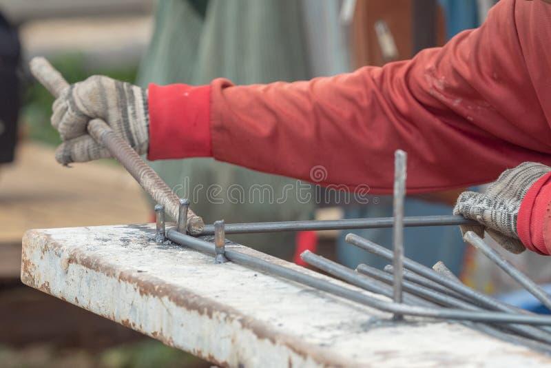 Barra d'acciaio del pacco del guanto di uso del muratore nel cantiere immagine stock