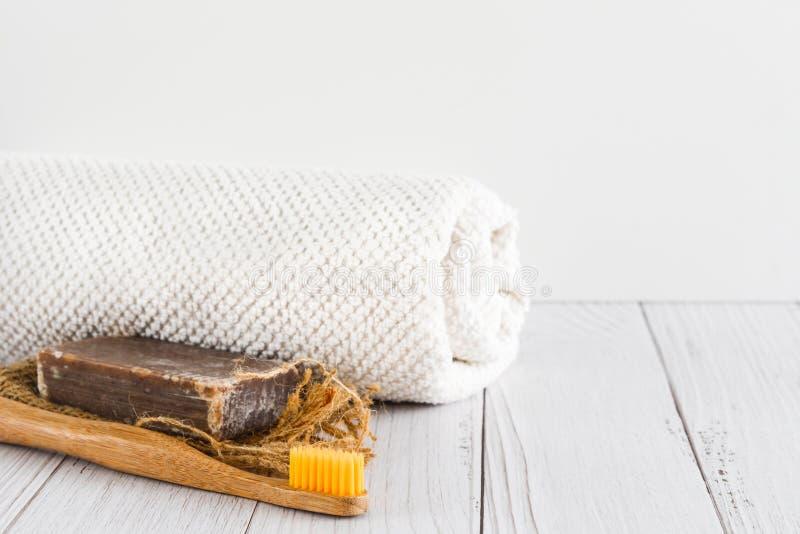 Barra da escova de dentes orgânica feito a mão natural do sabão, a de bambu e e da toalha branca no fundo branco, espaço vazi fotografia de stock royalty free