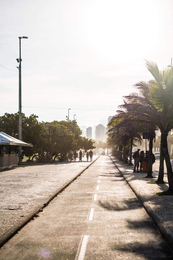 Barra da Tijuca boardwalk on a beatiful afternoon, withbuildings in the background. Rio de Janeiro, orange flare royalty free stock photography