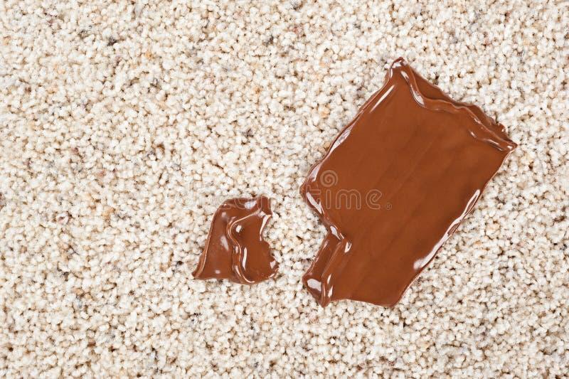 Barra de chocolate caída en la alfombra fotografía de archivo libre de regalías