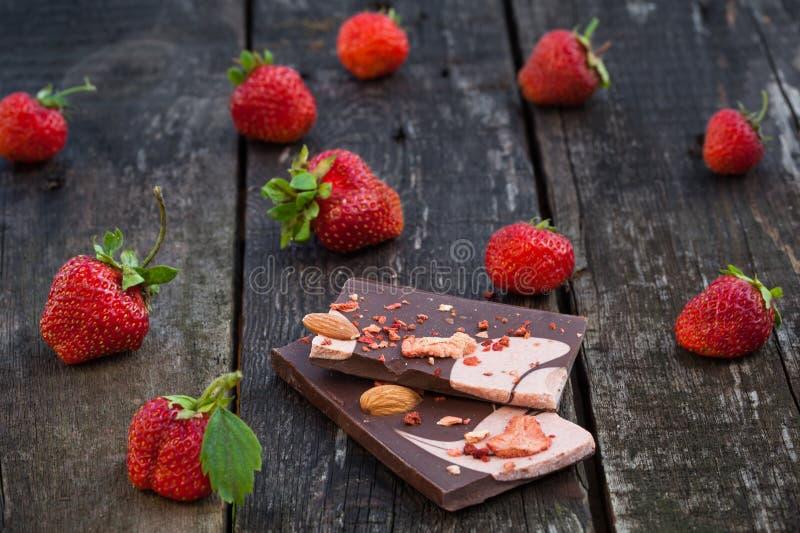 A barra de chocolate com fatias secadas da morango e fresco feitos a mão sejam imagens de stock