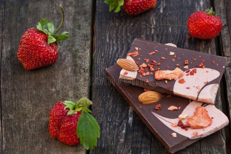 A barra de chocolate com fatias secadas da morango e fresco feitos a mão sejam imagens de stock royalty free