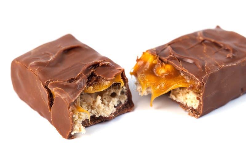 Barra de chocolate con el caramelo aislado en blanco fotografía de archivo