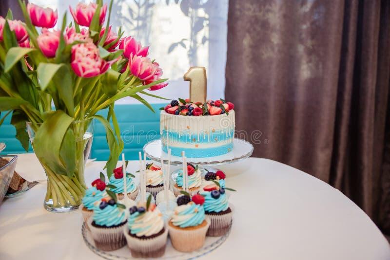Barra de chocolate decorada com doces, queques e bolo para a primeira festa de anos E imagem de stock