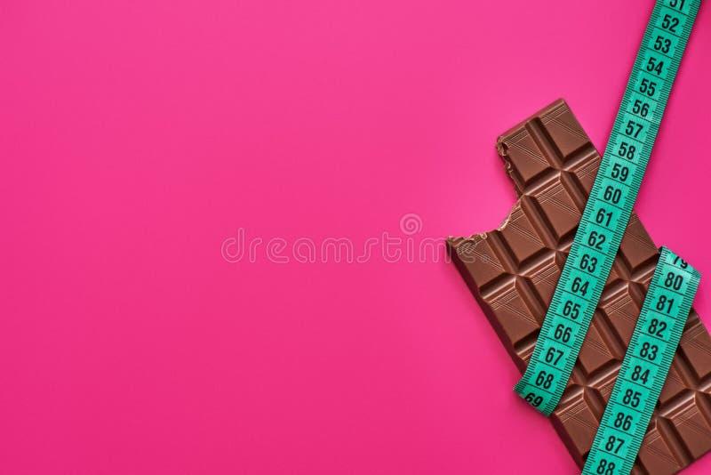Barra de chocolate envuelta con la cinta de la medida aislada en fondo rosado fotos de archivo libres de regalías