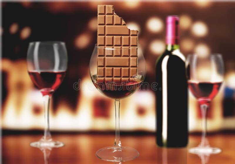 Barra de chocolate no vidro de vinho no fundo imagens de stock
