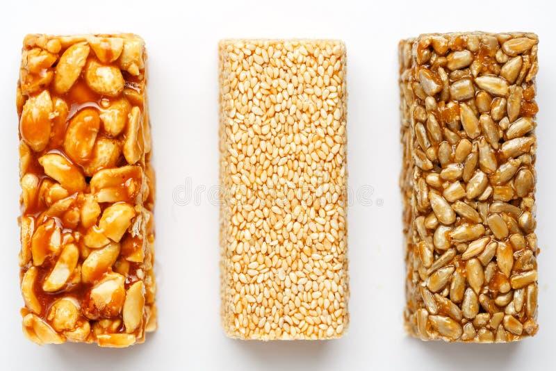 Barra de granola del grano con los cacahuetes, el sésamo y las semillas en fila en un fondo blanco Barras clasificadas de la opin fotografía de archivo