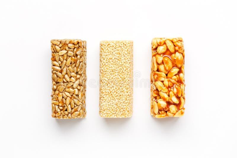 Barra de granola del grano con los cacahuetes, el sésamo y las semillas en fila en un fondo blanco Barras clasificadas de la opin imágenes de archivo libres de regalías