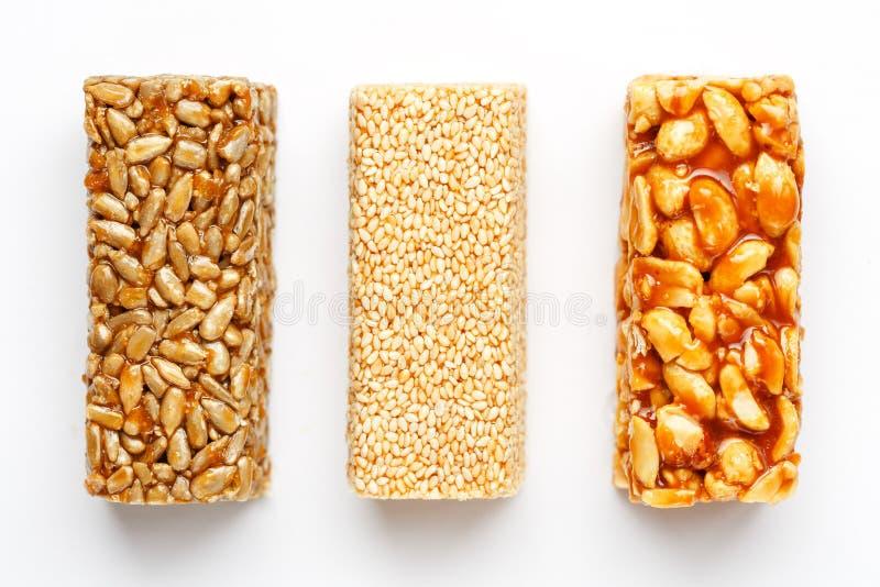 Barra de granola del grano con los cacahuetes, el sésamo y las semillas en fila en un fondo blanco Barras clasificadas de la opin foto de archivo libre de regalías