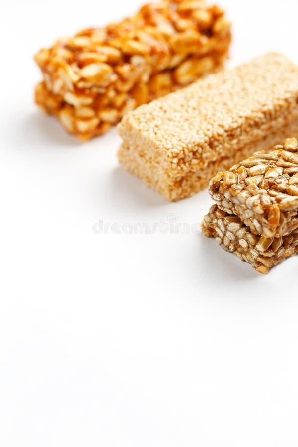 Barra de granola del grano con los cacahuetes, el sésamo y las semillas en fila en un fondo blanco Barras clasificadas de la opin imagenes de archivo