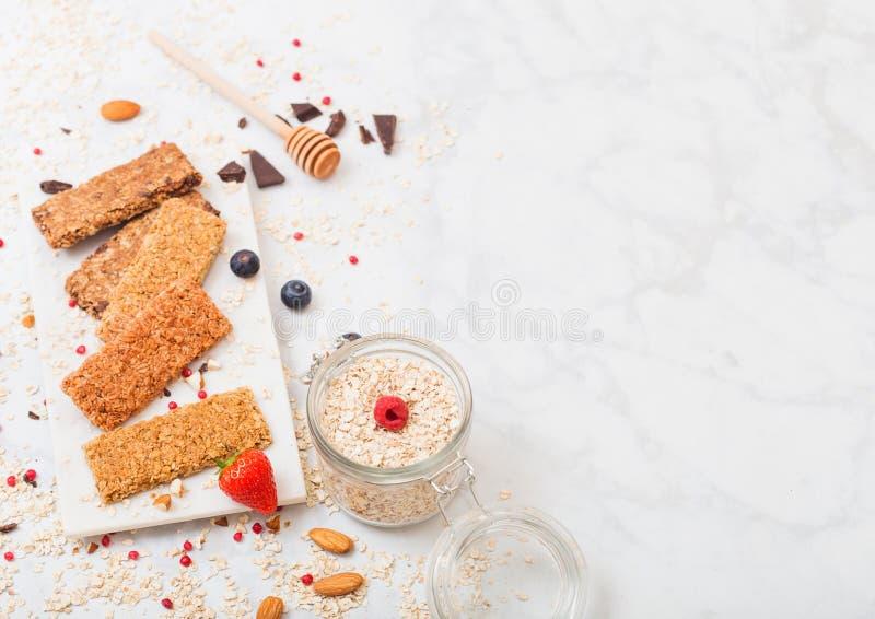 Barra de granola orgánica del cereal con las bayas en el tablero de mármol con la cuchara de la miel y el tarro de avena en el fo imagen de archivo libre de regalías