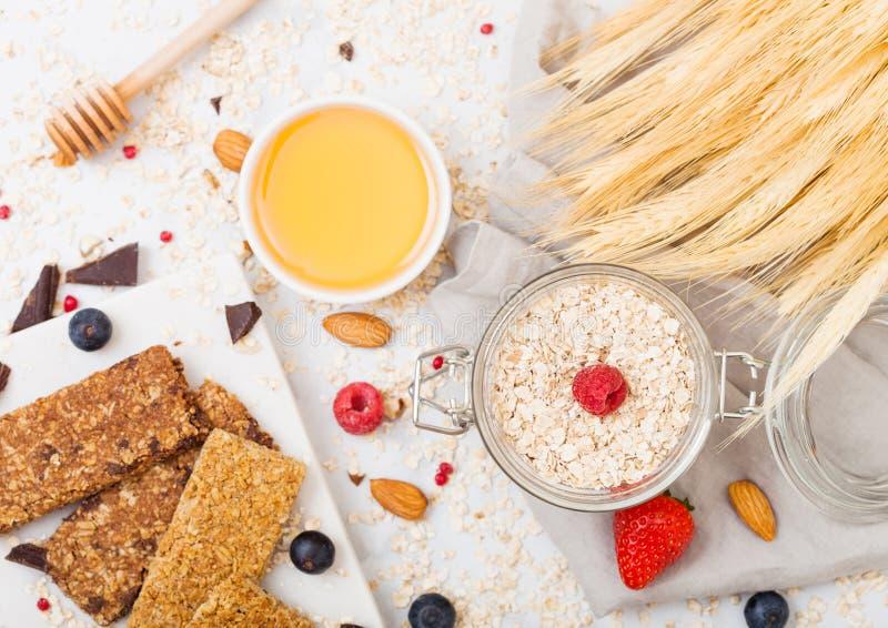 Barra de granola orgánica del cereal con las bayas en el tablero de mármol con la cuchara de la miel y el tarro de la avena y de  imagen de archivo libre de regalías