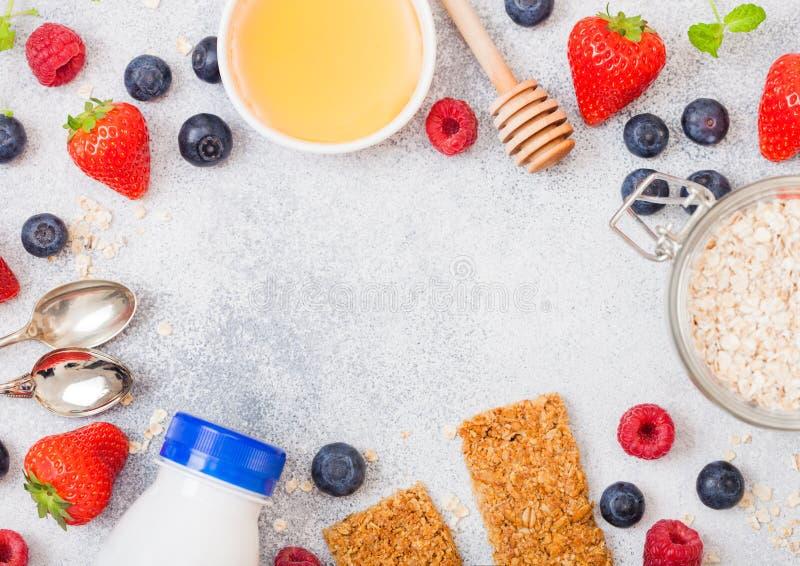 Barra de granola orgánica del cereal con las bayas con la cuchara de la miel y el tarro de la avena y de la botella de bebida de  imagen de archivo libre de regalías