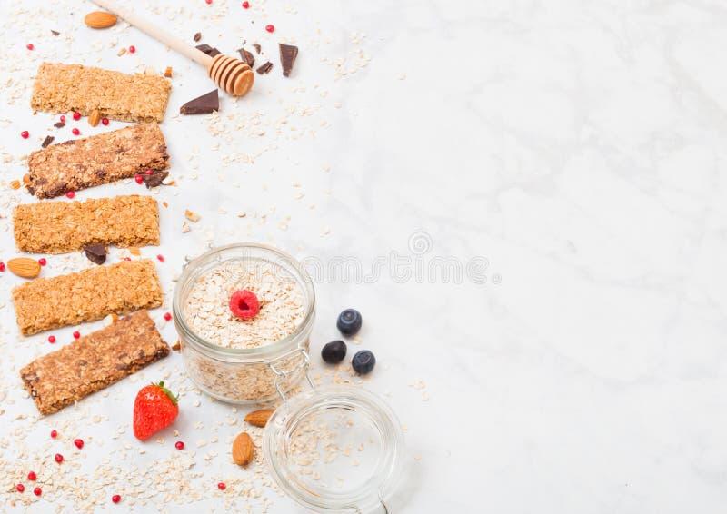 Barra de granola orgánica del cereal con las bayas con la cuchara de la miel y el tarro de avena en el fondo de mármol Visión sup imagenes de archivo