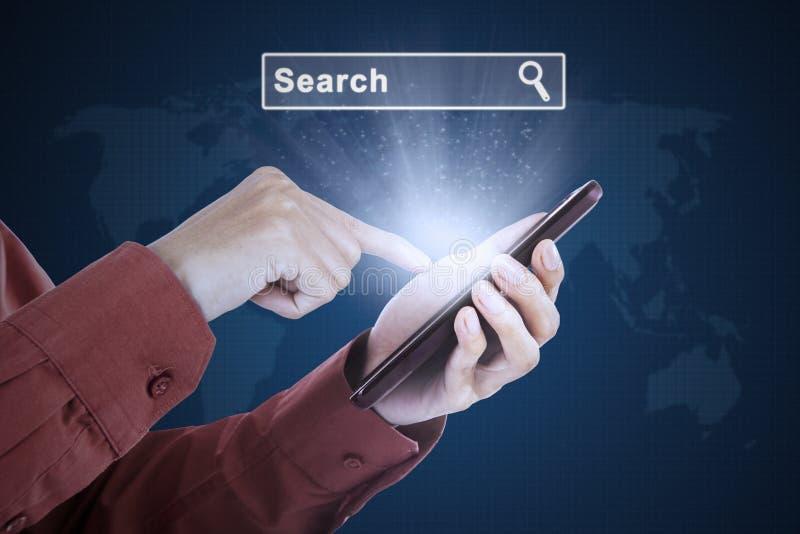 Barra de la búsqueda del presionado a mano en smartphone foto de archivo