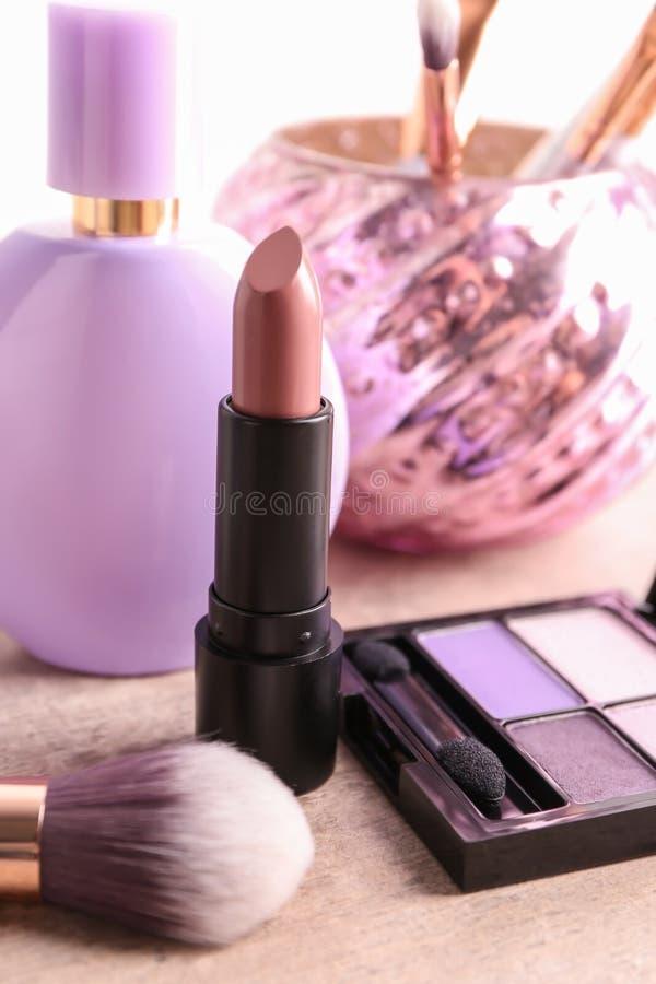 Barra de labios hermosa y otros cosméticos en la tabla imagenes de archivo