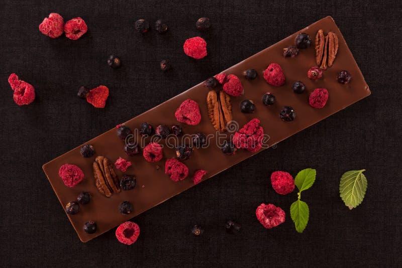 Barra de lujo del chocolate con leche con la fruta seca imagen de archivo