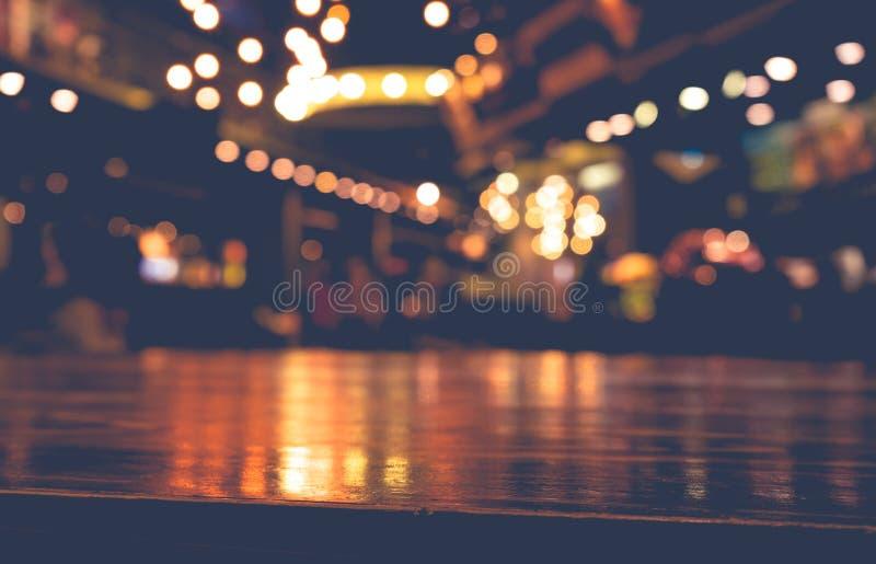 Barra de madeira vazia do tampo da mesa no restaurante do café do borrão no fundo escuro fotografia de stock