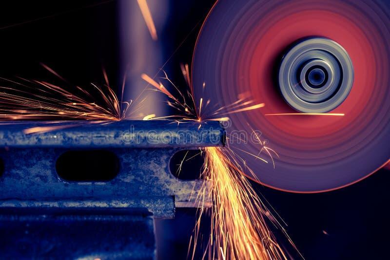 Barra de metal que está sendo cortada com o moedor bonde com voo da faísca, foco seletivo imagens de stock
