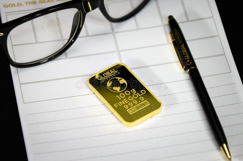 Barra de oro con la pluma y las lentes fotografía de archivo