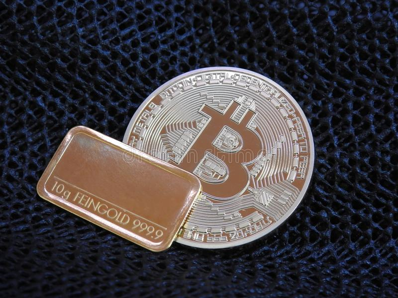 Barra de oro de Bitcoin y de oro foto de archivo