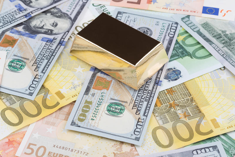 Barra de oro en dólares y euros fotografía de archivo libre de regalías