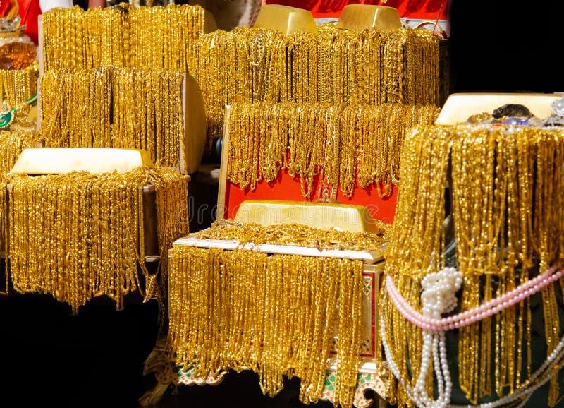 A barra de ouro e a colar do ouro muitos penduram na foto preta do fundo da textura da bandeja de veludo fotos de stock