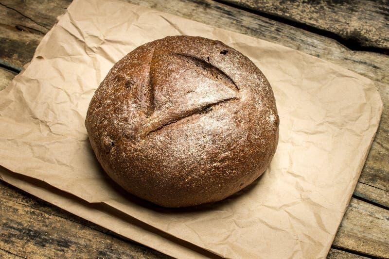 Barra de pan cocida fresca en bolsa de papel en la tabla de madera imagen de archivo libre de regalías