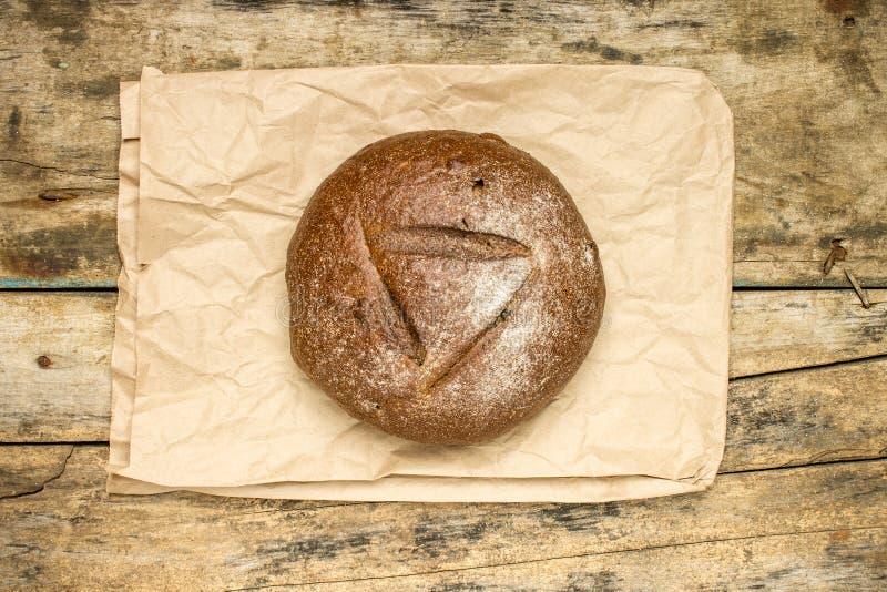 Barra de pan entera con la bolsa de papel en fondo de madera resistido imágenes de archivo libres de regalías