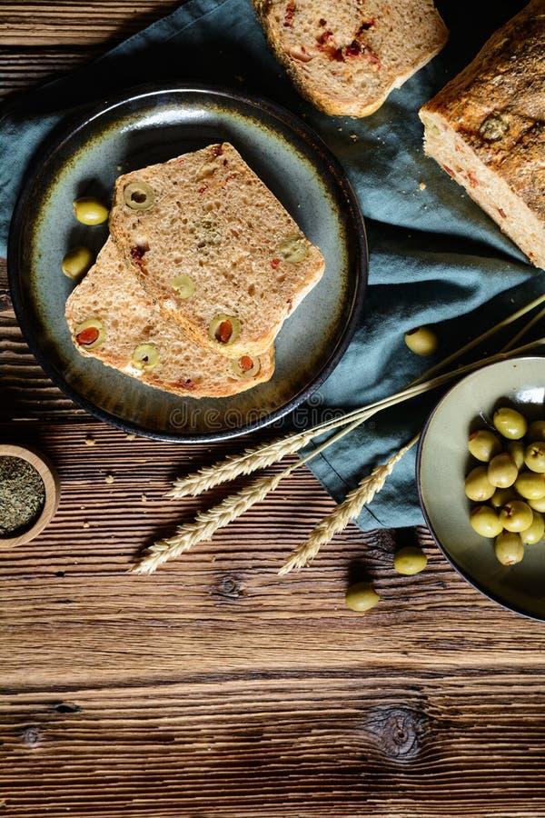 Barra de pan hecha en casa con el tomate y las aceitunas secados al sol foto de archivo