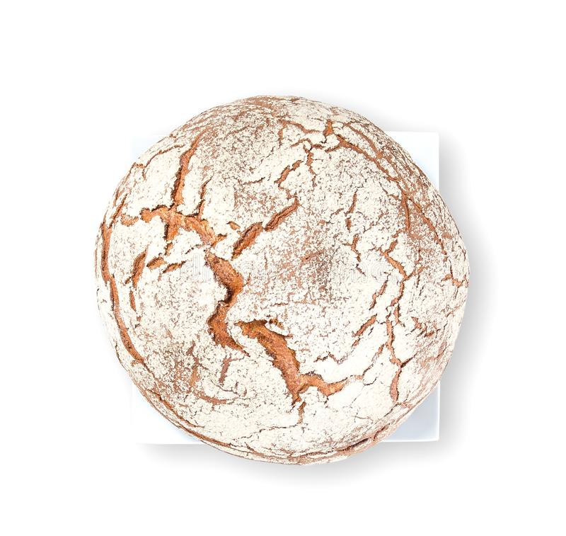 Barra de pan marrón redonda con la harina asperjada en el top en una placa de la casilla blanca en el fondo blanco fotos de archivo